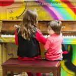 Kids playing on a Play me I'm yours street piano, St Pancras